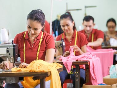 portrait of asian workers in garment factory sewing with industrial sewing machine