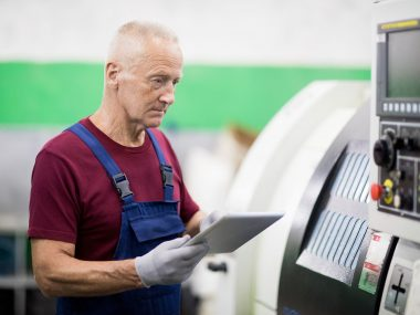 Gloved senior worker with touchpad searching for ways of problem solving while standing by industrial machine