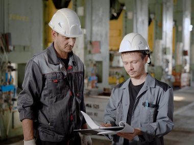 Portrait of a factory worker and crew chief talking about work process, holding documents. Inspection of assembly line, industrial plant inspector.