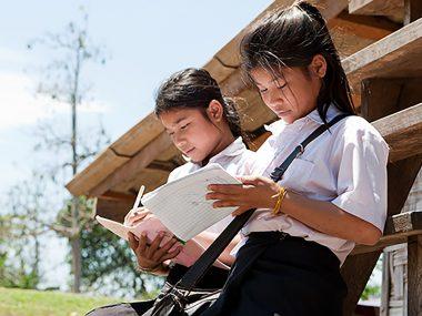 Studentinnen von Asien, beim Lernen vor dem Haus im Freien