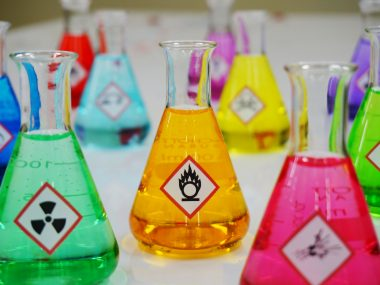 Many of Erlenmeyer flask with colorful solution and Variety type of chemical hazard warning symbols labels. Focus on Oxidizing sign,symbol.