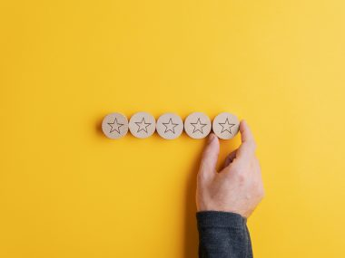 Male hand placing five wooden cut circles with stars on them in a row over bright yellow background. Conceptual image of quality and service.