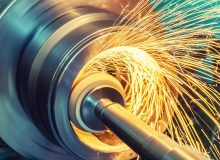 Internal grinding of a cylindrical part with an abrasive wheel on a machine, sparks fly in different directions. Metal machining.