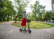 A young woman with purple hair rides an electric scooter in a park. A stylish girl with a shaved temple in a plaid shirt, a long red skirt and a bow tie is riding around the city on a modern device