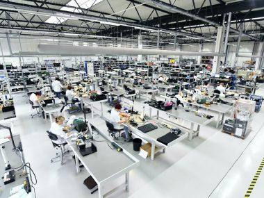Halbleiterindustrie: Arbeiter montieren elektronische Bauteile in einer Fabrik // Semiconductor industry: workers assemble electronic components in a factory